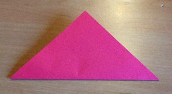 Das Origamipapier wird fuer die Papiertulpe einmal in der Mitte zu einem Dreieck gefaltet