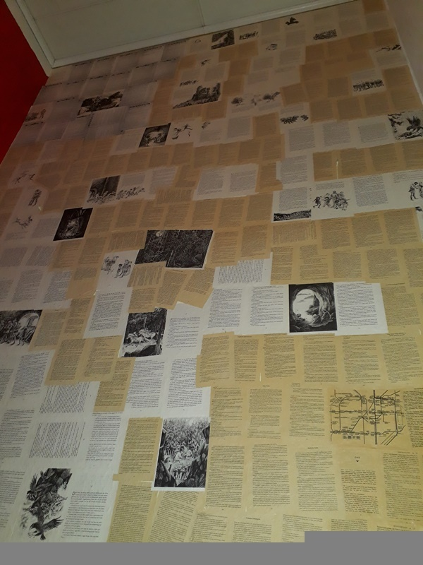 Eine Wand tapeziert mit Buchseiten zu finden bei Autorin Judith Vogt